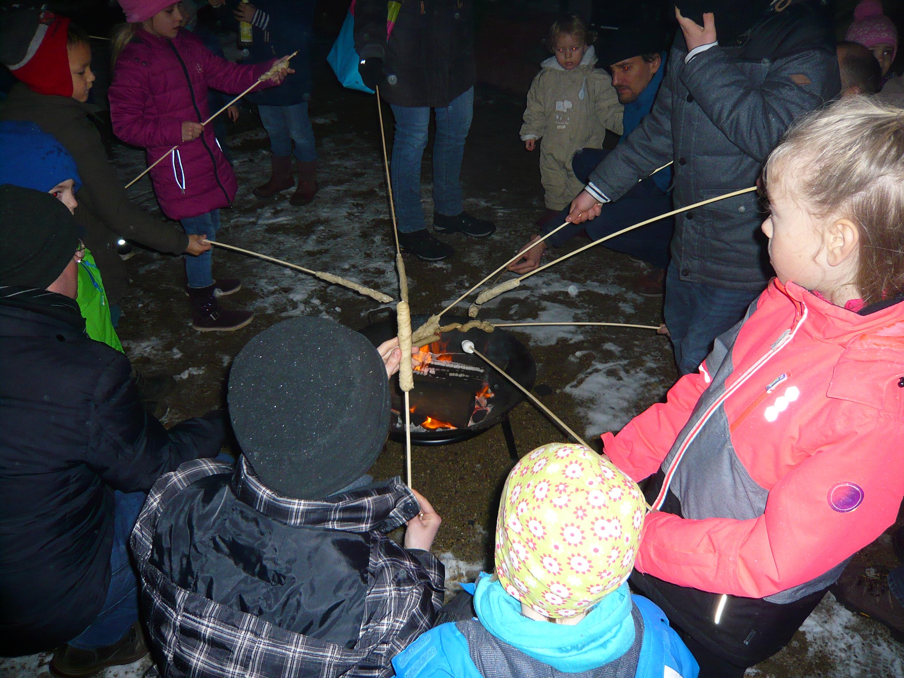 17 Kids und zahlreiche Erwachsene beim Winter-Stockbrot-Feuer vor dem Quartierladen